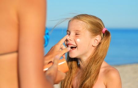 mother and daughter: Mother smearing her daughter with sunblock Stock Photo