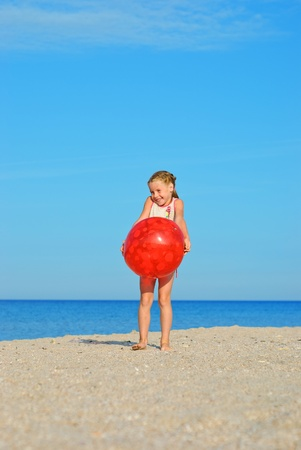 Happy little girl with red ball on the beach photo
