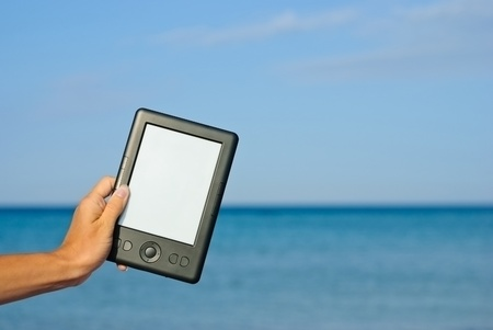 Female hand holding an e-book against the sea