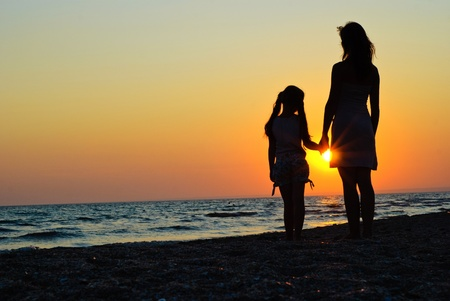Mother and daughter walking on the beach