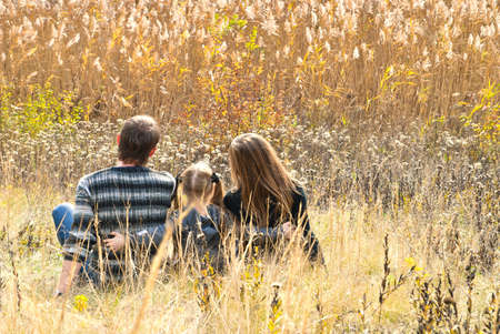 Mother, father and daughter sitting at the meadow in autumn