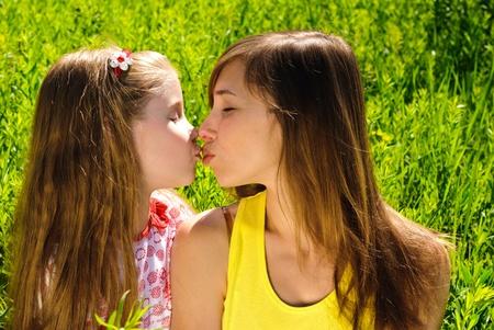 Kissing junge Mutter und kleine Tochter im Freien. Sonnigen Sommertag.