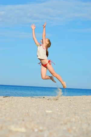 Jumping little girl on the beach