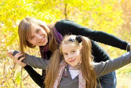 Smiling young mother with little daughter outdoor. Autumn day.