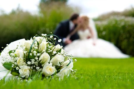 Bridal bouquet of white roses on a green meadow and blurred newlyweds Stock Photo
