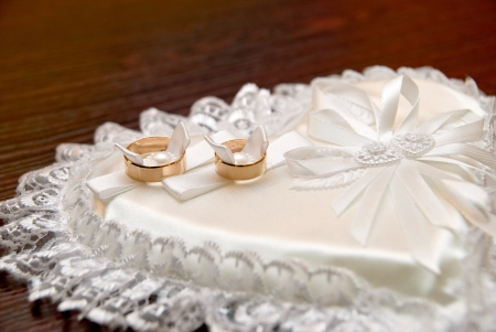 Two wedding rings on a heart-shaped pad photo