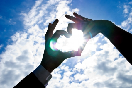 Two hands of newlywed looks like heart with sun inside