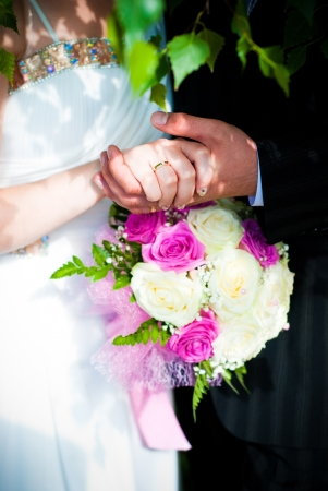 Bridal bouquet of white roses and hands of newlywed photo