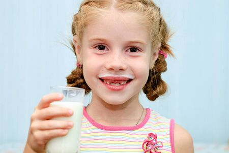 Portrait of a little toothless girl a glass of milk