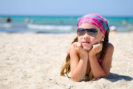 Little girl in sunglasses on the beach