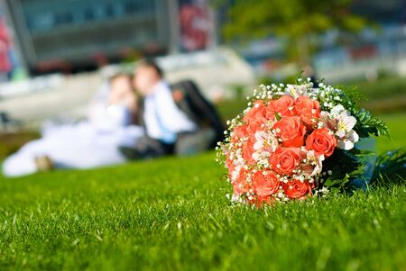 Bridal bouquet of red roses on a green meadow and blurred newlyweds Stock Photo