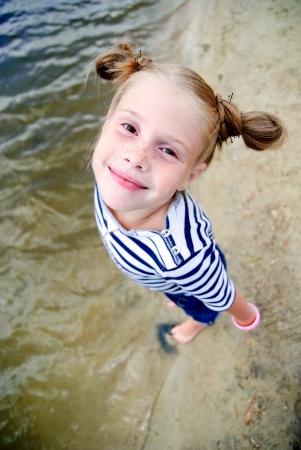 Kleines Mädchen am Strand in die Kamera schaut von unten nach oben