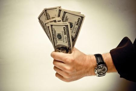 Der Stapel der US Federal Reserve Notes $ 100 in die Hand eines Mannes. Old style Foto. Lizenzfreie Bilder