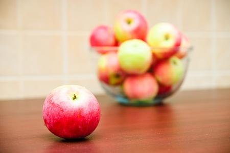 Saftigen Apfel und verschwommenes Glasschale mit Äpfeln gefüllt Lizenzfreie Bilder