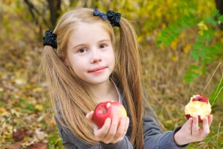 Kleines Mädchen isst Apfel im Freien