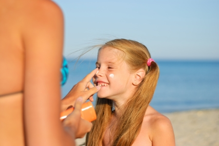 Mother smearing her daughter with sunblock Stock Photo