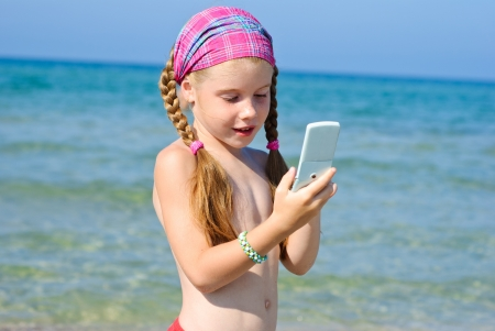 A little girl talks to mobile phone on the beach photo
