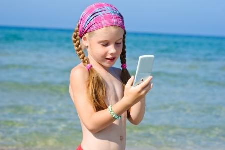 Ein kleines Mädchen spricht mit Handy am Strand