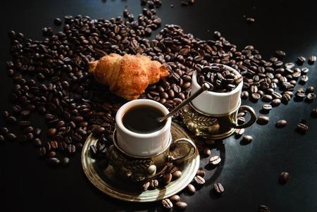 Bild von zwei Tassen Kaffee mit Croissant.