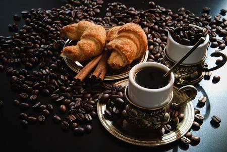 Zwei Tassen Kaffee mit Croissants und Stücke von Zimt