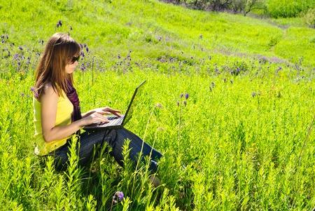 Junge schöne Frau mit Laptop im Freien. Sonnigen Sommertag.