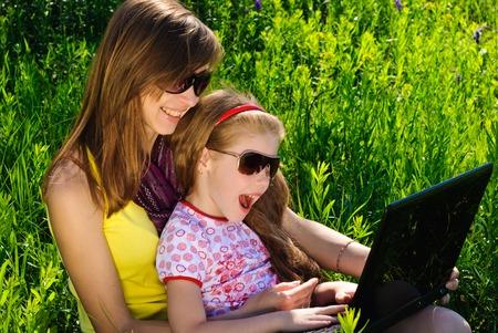 Lächelnde junge Mutter mit kleinen Tochter. Sonnigen Sommertag.