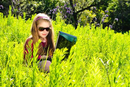 Smiling kleines Mädchen mit Laptop im Freien. Sonnigen Sommertag.