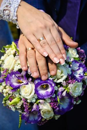 Hände des Bräutigams und der Braut mit Trauringe auf der Oberseite der Strauß der Braut