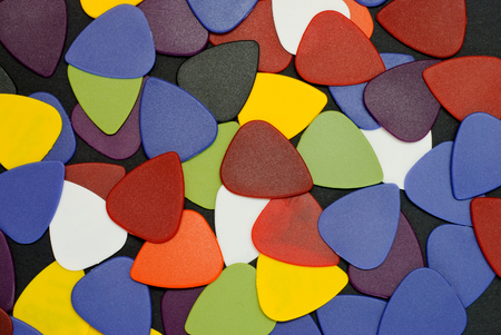 A pile of cheap guitar picks on a black background. Close up view.