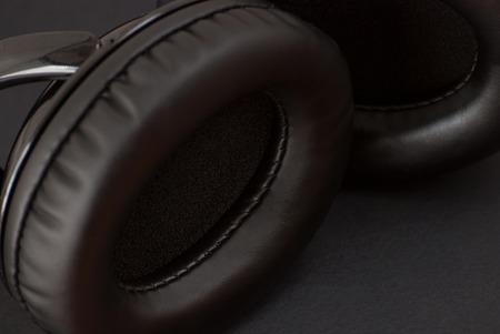 Black monitor headphones. Close up view. Low key shot.