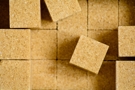Cubes of brown cane sugar. Close-up top view.