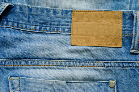 Old blue denim jeans wirh blank label. Close up view. Stock Photo