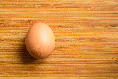 Fresh natural raw chicken egg on a wooden background. Close up top view. Stock Photo