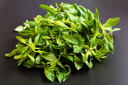 A bunch of fresh green mint on a black background. Close-up top view.