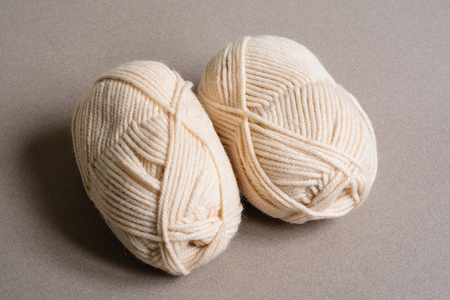 Two rolls of beige wool on a gray background. Top view. Stock Photo