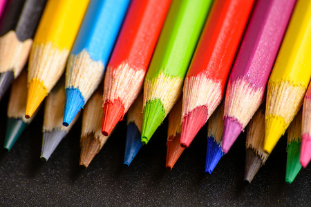 Colorful pencils on a black background. Close-up top view.