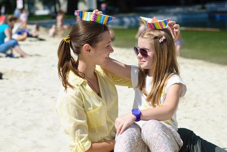 Kleines Mädchen mit Mutter scherzt am Strand in einem hellen sonnigen Tag