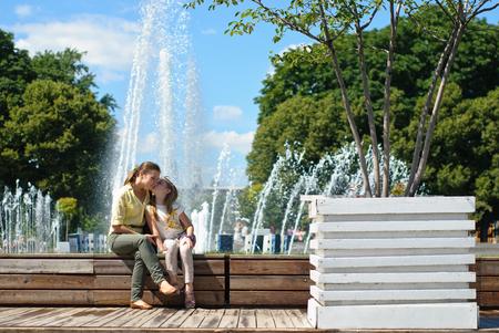 Kleines Mädchen mit Mutter umarmt in den Park in einem hellen sonnigen Tag