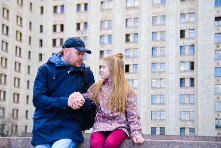 Father talking to daughter holding her hands against the wall of the building Stock Photo