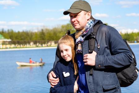 Vater umarmt Tochter gegen einen Teich mit einem schwimmenden Boot an einem hellen sonnigen Tag