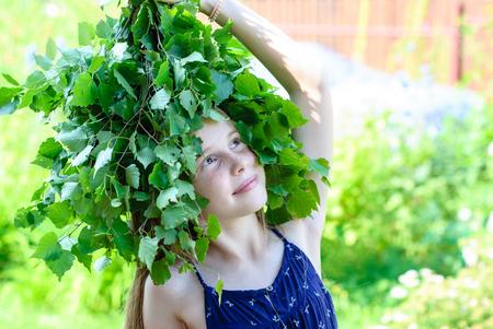 Schönes kleines Mädchen mit einem Kranz aus grünen Blättern auf dem Kopf.