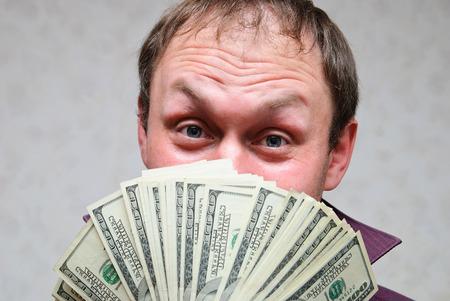 Der reiche Mann lächelt und zeigt Bündel von Hundert-Dollar-Scheinen.