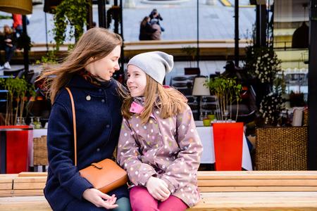 Kleines Mädchen mit Mutter umarmt in der Stadtstraße in einem windigen Tag