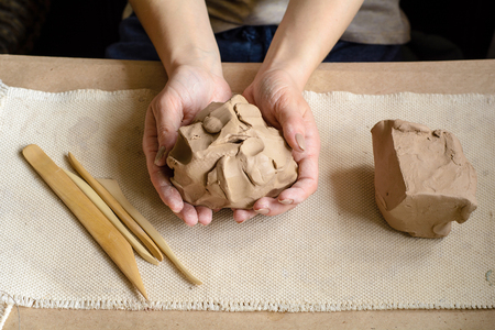 A piece of clay in the female hands of a master. Handmade crsft background. Stock Photo