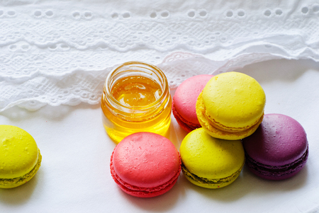 Colorful macaroons or macaron and jar of honey on a white tablecloth Stock Photo