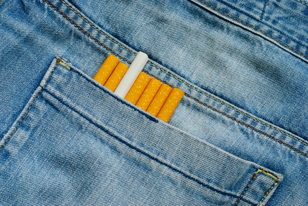 Cigarettes in old blue denim jeans pocket. Close up view.