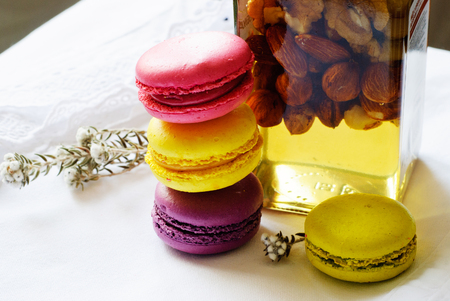 Colorful macaroons or macaron and jar of honey and nuts on a white tablecloth