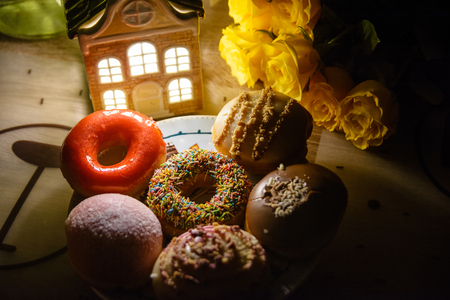 Various beautiful donuts and flowers in the evening home decor Stock Photo