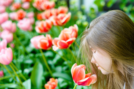 Young happy teenage girl sniffing a tulip in a meadow