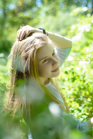 Young beautiful teenage girl posing in a park among green foliage Stock Photo